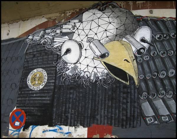 Un graffito raffigurante l'acquila simbolo degli USA equipaggiata con armi di spionaggio digitale