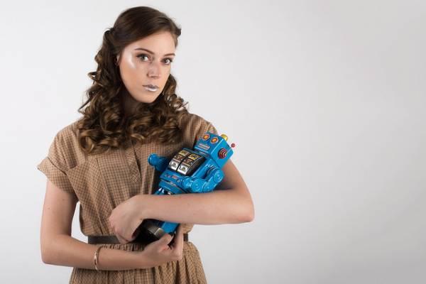 Una donna ha in braccio un piccolo robot come se fosse un bambino.