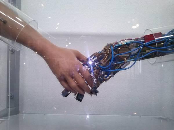 Una mano robotica stringe una mano umana.