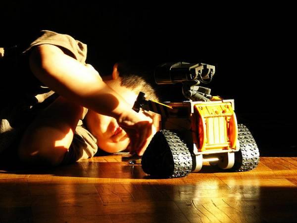 Un bimbo gioca con un robot.