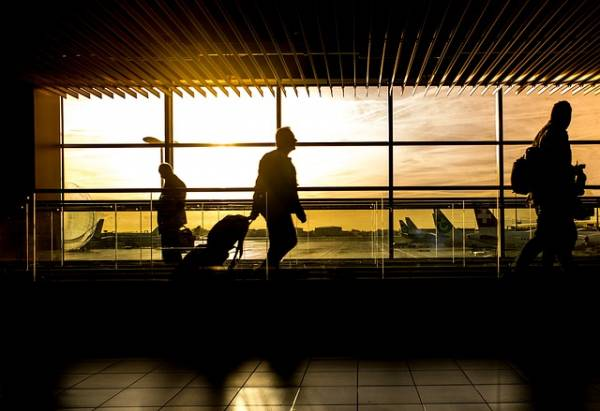 L'area di un aeroporto con dei viaggiatori e le loro valigie